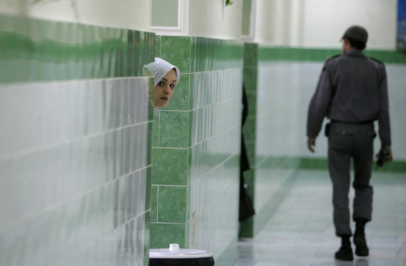 TO GO WITH AFP STORY IRAN-JUSTICE-PRISON-SOCIT BY PIERRE CELERIER  An Iranian inmate peers from behind a wall as a guard walks by at the female section of the infamous Evin jail, north of Tehran, 13 June 2006. AFP PHOTO/ATTA KENARE (Photo by ATTA KENARE / AFP)