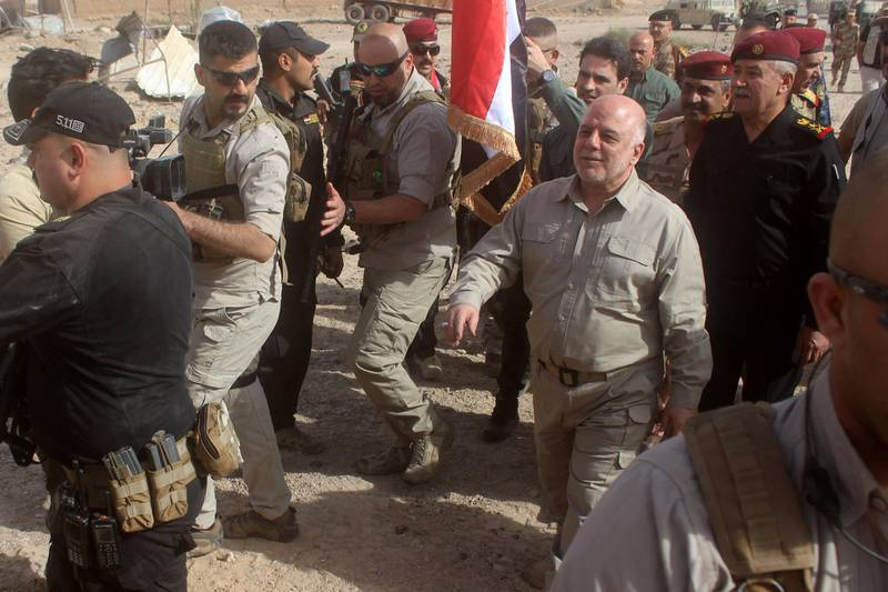 Iraqi Prime Minister Haider al-Abadi prepares to erect a national flag in Al-Qaim on November 5, 2017, after troops retook the border town from Islamic State (IS) group jihadists. The fall of Al-Qaim leaves IS fighters in Iraq holding just the smaller neighbouring town of Rawa and surrounding pockets of barren desert along the Euphrates river. / AFP PHOTO / MOADH AL-DULAIMI