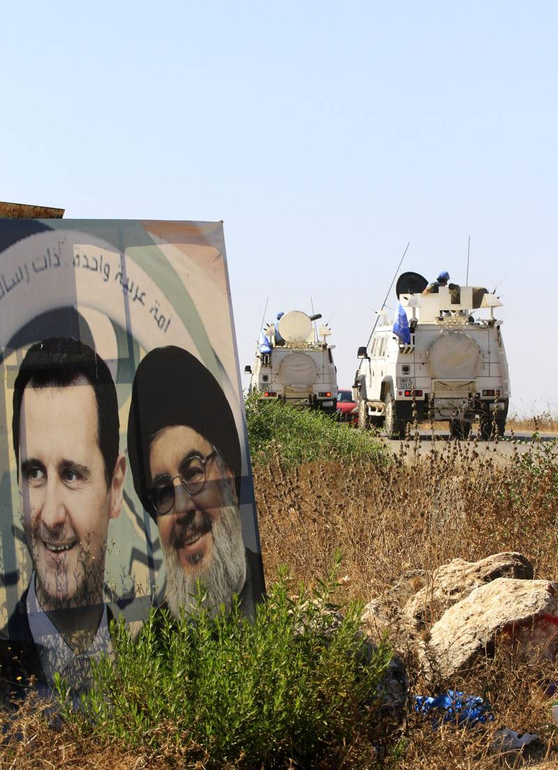"""Military vehicles belonging to the United Nations Interim Forces in Lebanon (UNIFIL) drive past posters of the Lebanese Shiiite Hezbollah movement leader Hasan Nasrallah (R) and Syrian President Bashar al-Assad, on a road near the southern Lebanese village of Marjayoun, on August 26, 2019.  Nasrallah yesterday threatened Israel after a """"drone attack"""" on the Lebanese Shiite movement's Beirut stronghold, vowing to """"do everything"""" to thwart future attacks. Hezbollah, considered a terrorist organisation by Israel and the United States, is a major political actor in Lebanon and a key government backer in war-torn Syria. / AFP / Mahmoud ZAYYAT"""
