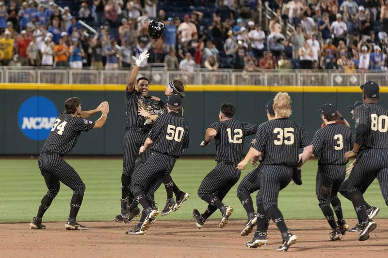 Vanderbilt's Jayson Gonzalez, second from left, tosses his helmet while celebrating with teammates after driving in the winning run against Arizona in the 12th inning of a baseball game in the NCAA College World Series on Saturday, June 19, 2021, in Omaha, Neb. (AP Photo/Rebecca S. Gratz)