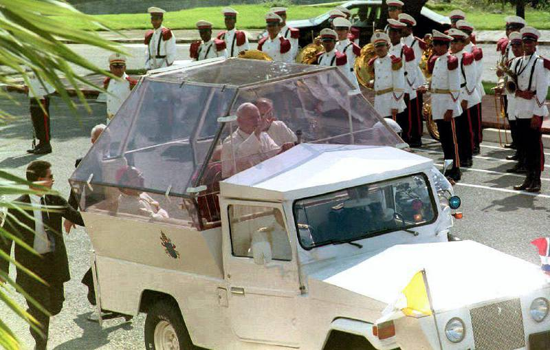 Pope John Paul II waves to people gathered outside the gates of the Presidential Palace in Santo Domingo 10 October, 1992 as he arrives to meet with President Joaquin Balaguer. The Pope, who is on his third visit to the Dominican Republic, is scheduled to inaugurate the IV Latin American cardinals and bishops conference 12 Oct. (Photo by MICHEL GANGNE / AFP)