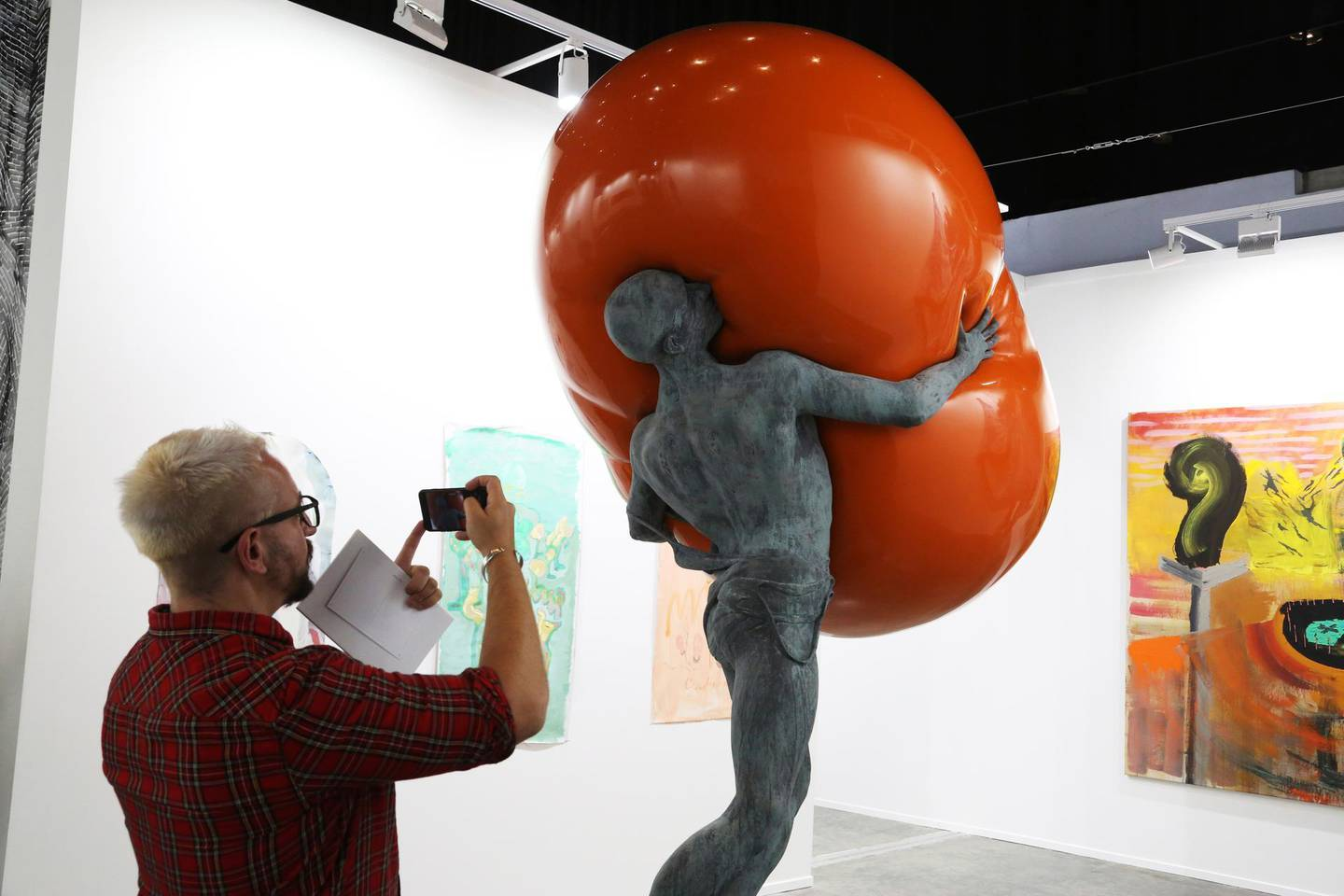 """A man takes a photo of Iranian artist Mohammad Hossein Gholamzadeh's 2019 work """"Farewell to Proserpina"""" at Art Dubai in Dubai, United Arab Emirates, Tuesday, March 19, 2019. Art Dubai is marking its 13th edition with an exhibition running March 20 through March 23. (AP Photo/Jon Gambrell)"""