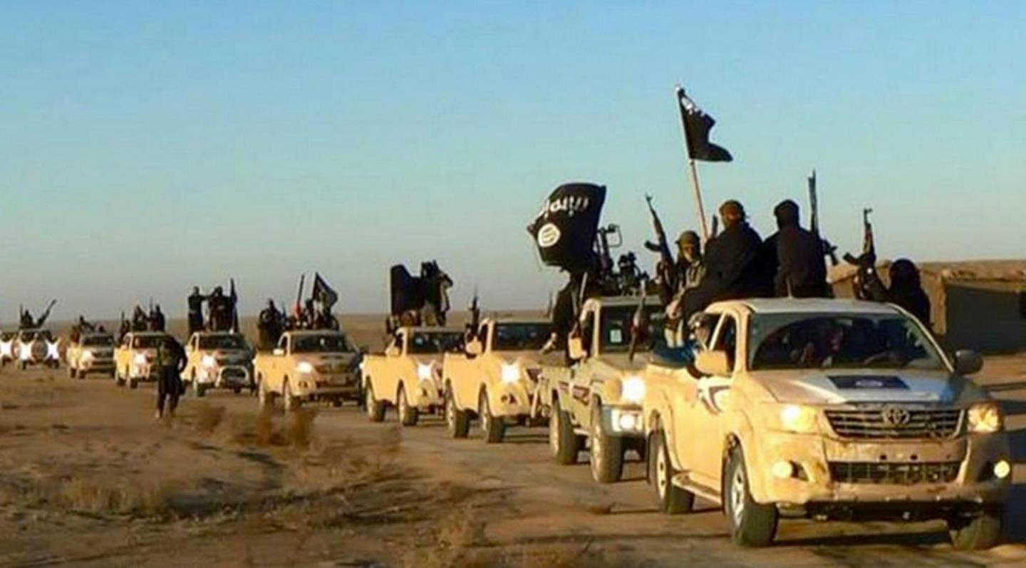FILE - In this undated file photo released online in the summer of 2014 on a militant social media account, which has been verified and is consistent with other AP reporting, militants of the Islamic State group hold up their weapons and wave its flags on their vehicles in a convoy on a road leading to Iraq, in Raqqa, Syria. A military spokesman said Monday, Dec. 3, 2018 that the U.S.-led coalition has targeted a senior member of the Islamic State group who was involved in the 2014 killing of American aid worker Peter Kassig. (Militant photo via AP, File)