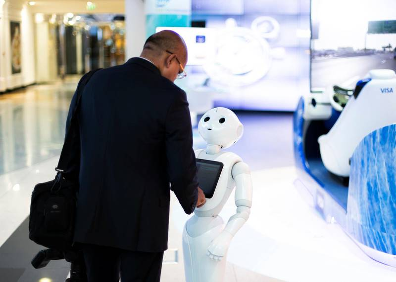 """DUBAI, UNITED ARAB EMIRATES. 3 NOVEMBER 2019. A man interacts with Pepper at Emirates NBD branch in Emirates Towers.Dubai Future Foundation (DFF) launched Dubai Future Week which offers a schedule of community events and interactive workshops at AREA 2071 in Emirates Tower, as part of efforts to offer a global futuristic experience that promotes technological knowledge and applications.Under the theme: """"Imagining, Designing and Executing the Future"""", participants will have the opportunity to preview international films that envision the future, play Human Experience 2.0, an awareness game that introduces futuristic technologies, marvel at the Future Exhibition of images, shopping and the future of food, and engage in Future Dialogues which will explore various sectors such as education, workforce, economics and transportation.(Photo: Reem Mohammed/The National)Reporter:Section:"""