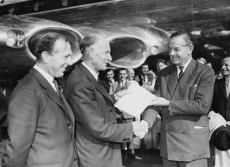 British aircraft engineer Geoffrey de Havilland (1882 - 1965, centre) hands over the articles of a new Comet IV jet airliner to Sir Gerard d'Erlanger (right), Chairman of BOAC (British Overseas Airways Corporation), at London Airport, 30th September 1958. On the left is Aubrey F. Burke, Managing Director of the de Havilland Aircraft Manufacturing Company. (Photo by J. Wilds/Keystone/Hulton Archive/Getty Images)