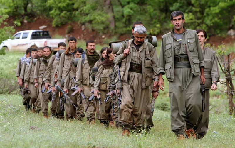 """FILE - in this Tuesday, May 14, 2013 file photo, a group of armed Kurdish fighters from the Kurdistan Workers Party (PKK) enter northern Iraq in the Heror area, northeast of Dahuk, 260 miles (430 kilometers) northwest of Baghdad, Iraq. A Kurdish rebel group says they are withdrawing from Iraq's Sinjar following threats of attack from Turkey. The Kurdistan Workers Party, or PKK, says in a statement Friday, March 23, 2018 the """"Iraqi government's position and the fact that the Kurdish community had managed to organize itself"""" have removed security fears in the area. (AP Photo/Ceerwan Aziz, File)"""