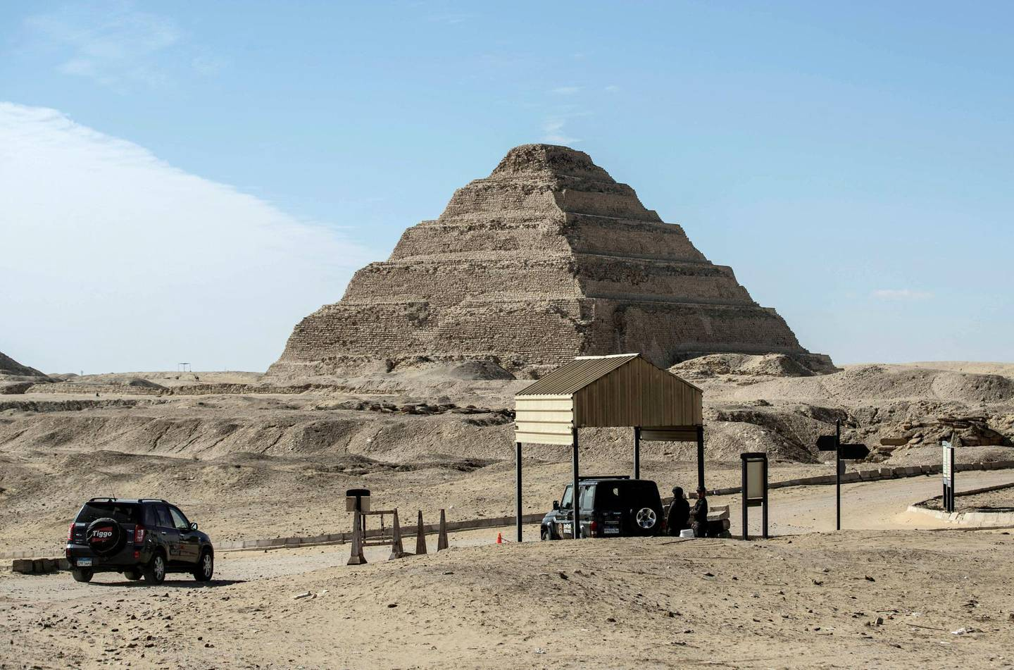Egyptian security officers man their station across from the step pyramid of Djoser at the Saqqara necropolis south of Cairo, on January 17, 2021. - Egypt announced the discovery of a new trove of treasures at the necropolis which lies 30kms south of the capital, including the funerary temple of Queen Naert, wife of King Teti, as well as burial shafts, coffins, and mummies dating back to nearly 3000 years ago during the New Kingdom. (Photo by Khaled DESOUKI / AFP)