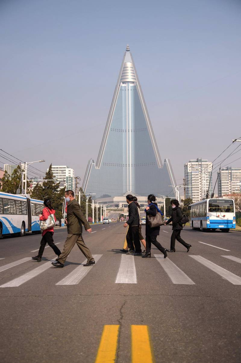 People wearing face masks walk across a street before the Ryugyong hotel (back C) on the occasion of the 108th birthday of late North Korean leader Kim Il Sung, known as the 'Day of the Sun', in Pyongyang on April 15, 2020. (Photo by KIM Won Jin / AFP)