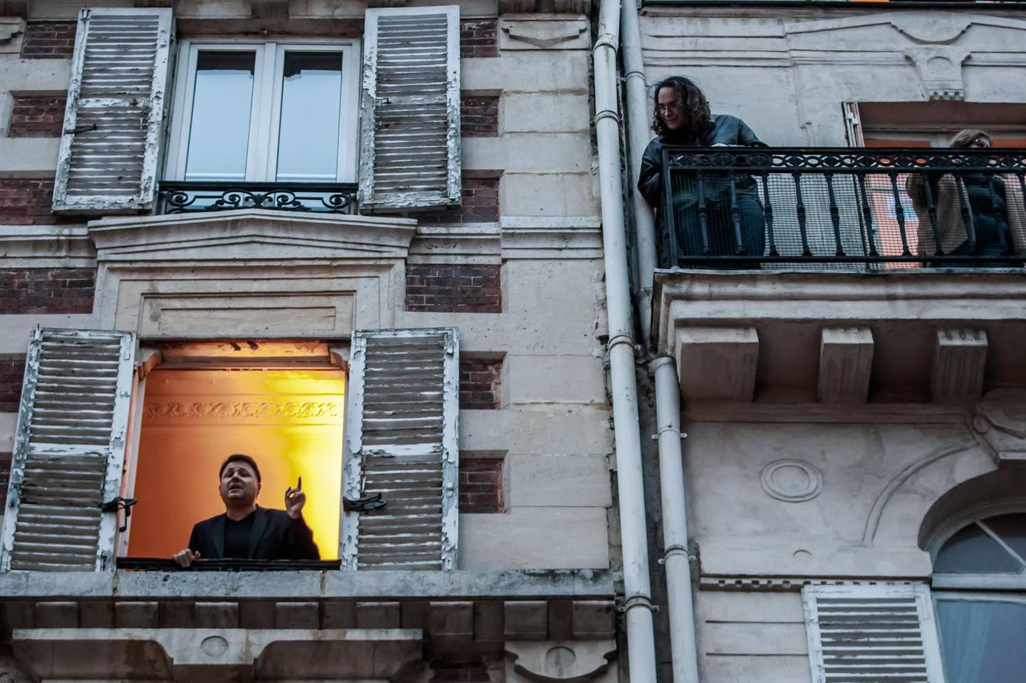 epa08312429 French tenor singer Stephane Senechal (L) sings at his window for the inhabitants of his street in Paris, France, 21 March 2020.  Senechal signs every evening since the beginning of containment measures decided by the government to lockdown France in an attempt to stop the widespread of the SARS-CoV-2 coronavirus causing the Covid-19 disease.  EPA/CHRISTOPHE PETIT TESSON