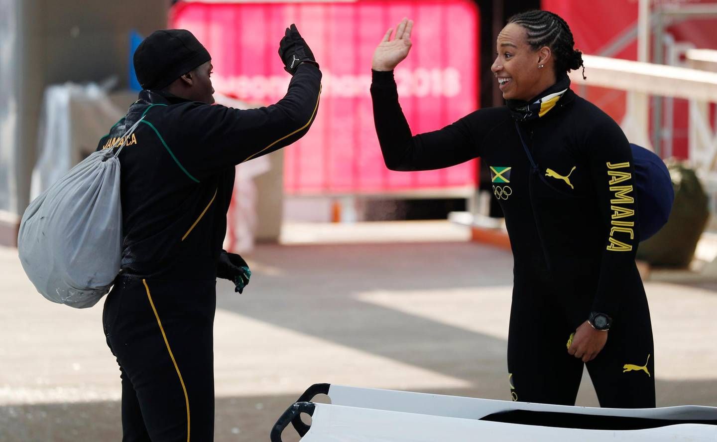 Bobsleigh – Pyeongchang 2018 Winter Olympics – Women's Training – Olympic Sliding Centre - Pyeongchang, South Korea – February 8, 2018 - Jazmine Fenlator-Victorian and Carrie Russell of Jamaica trade high-fives.  REUTERS/Edgar Su