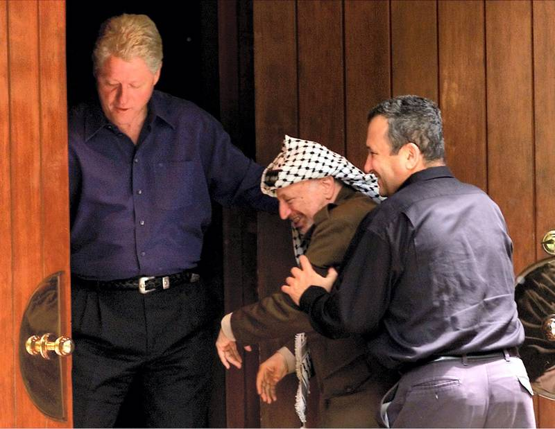 Israeli Prime Minister Ehud Barak (R) jokingly pushes Palestinian President Yasser Arafat (C) into the Laurel cabin on the grounds of Camp David as U.S. President Bill Clinton watches during peace talks, July 11. Arafat and Barak were insisting that the other proceed through the door first. Camp David is the venue where Egypt and Israel made peace in September 1978, and the Laurel cabin was the site of many of the meetings.  WM/RCS