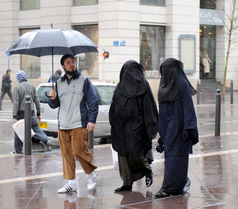 """Two veiled muslim women walk down a street in Marseille, southern France, on December 24, 2009. French President Nicolas Sarkozy's ruling party will push for a law banning the full-face Islamic veil in order to defend France from """"extremists"""".     AFP PHOTO MICHEL GANGNE / AFP PHOTO / MICHEL GANGNE"""