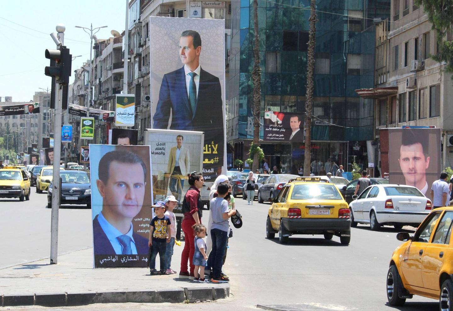 FILE PHOTO: People stand near posters depicting Syria's President Bashar al-Assad, ahead of the May 26 presidential election, in Damascus, Syria May 18, 2021. Picture taken May 18, 2021. REUTERS/Firas Makdesi/File Photo