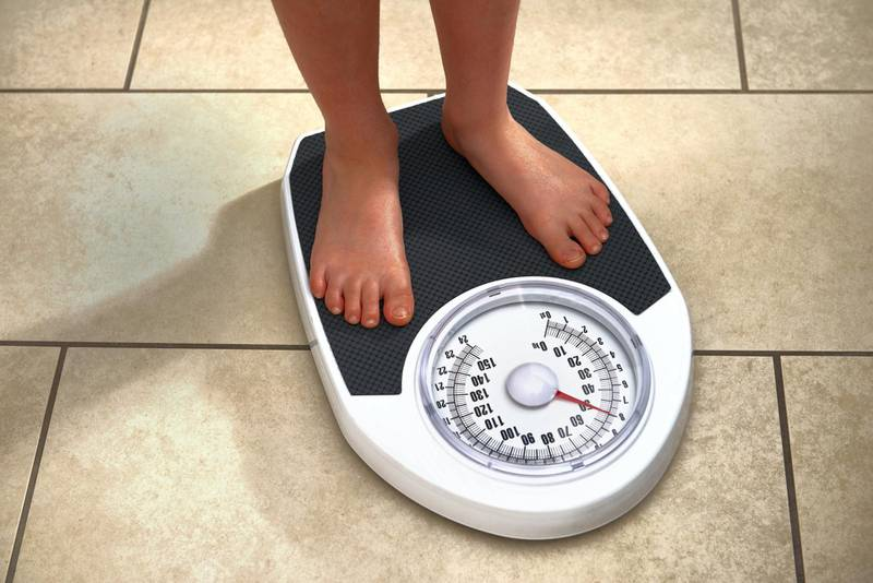8 year old boy weighing himself on bathroom scales at home
