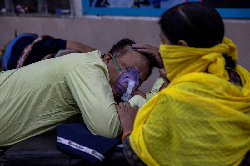 A woman takes care of her husband who is suffering from the coronavirus disease (COVID-19) as he waits to get admitted outside the causality ward at Guru Teg Bahadur hospital, amidst the spread of the disease in New Delhi, India, April 23, 2021. REUTERS/Danish Siddiqui