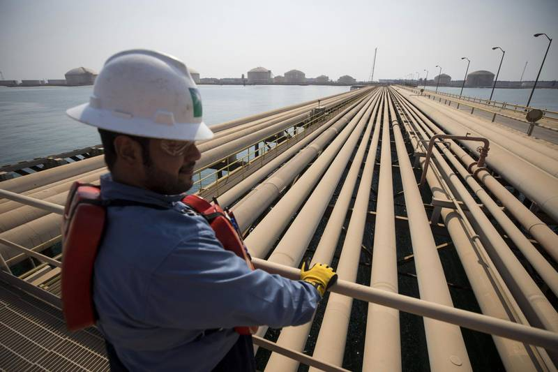 An employee looks out over oil transport pipelines on the Arabian Sea in Saudi Aramco's Ras Tanura oil refinery and oil terminal in Ras Tanura, Saudi Arabia, on Monday, Oct. 1, 2018. Saudi Arabiais seeking to transform its crude-dependent economy by developing new industries, and is pushing into petrochemicals as a way to earn more from its energy deposits. Photographer: Simon Dawson/Bloomberg