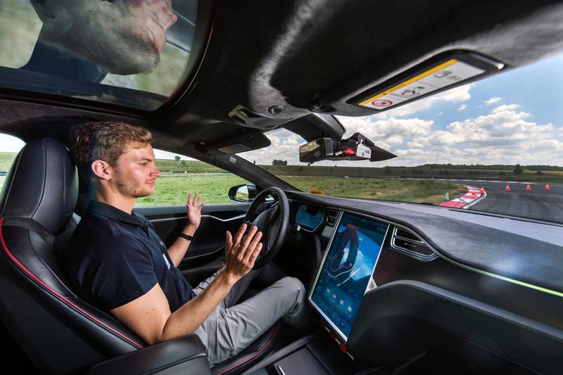 A test driver removes his hands from the steering wheel of a Tesla Motors Inc. Model S electric automobile fitted with self driving technology, developed by Robert Bosch GmbH, during the Bosch mobility experience in Boxberg, Germany, on Tuesday, July 4, 2017. Auto supplier Bosch will build a 1 billion-euro ($1.1 billion) semiconductor plant, the biggest single investment in its history, as the maker of brakes and engines prepares for a surge in demand for components used in self-driving vehicles. Photographer: Andreas Arnold/Bloomberg