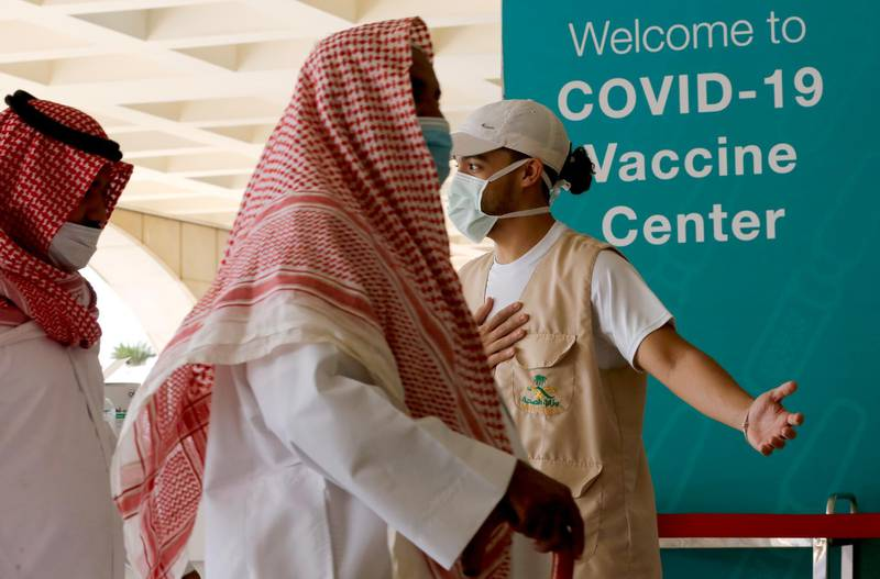 Saudis are greeted by a health worker as they enter a new coronavirus vaccination center at the Jiddah old airport, Saudi Arabia, Thursday, Jan. 14, 2021. The Saudi Ministry of Health has called on citizens and residents to take the vaccine for free. (AP Photo/Amr Nabil)