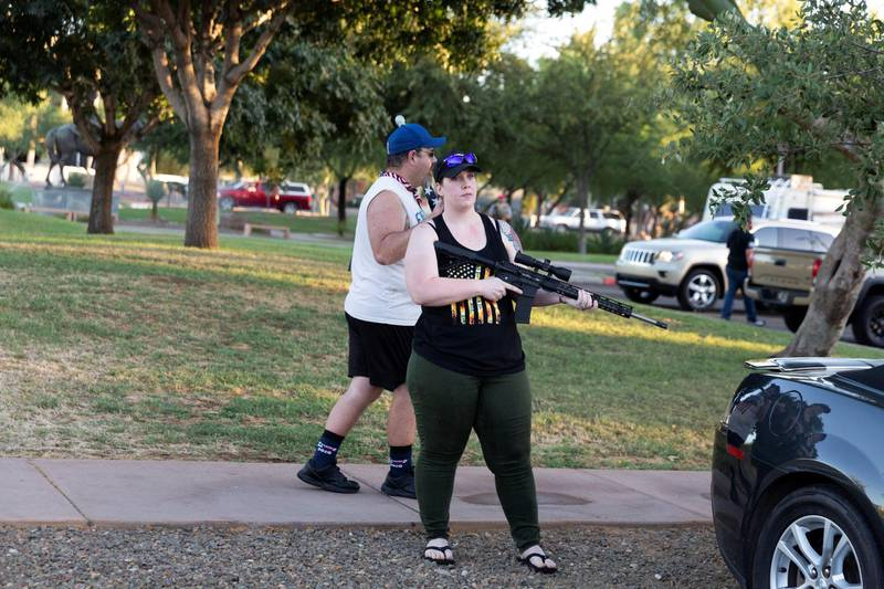 A woman holding a gun reacts to Black Lives Matter protesters who arrived at a rally against restrictions to prevent the spread of the coronavirus disease (COVID-19) in Phoenix, Arizona, U.S., July 4, 2020. REUTERS/Cheney Orr