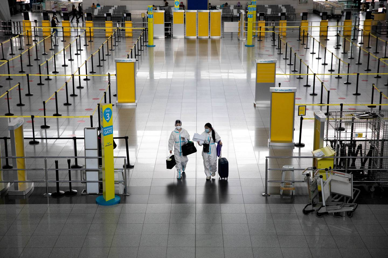FILE PHOTO: Passengers wearing hazmat suits for protection against the coronavirus disease (COVID-19) walk inside the Ninoy Aquino International Airport in Paranaque, Metro Manila, Philippines, January 14, 2021. REUTERS/Eloisa Lopez/File Photo