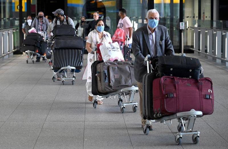 epa08397433 Passengers wear masks as they arrive at Heathrow Airport, in Britain, 02 May 2020.  Due to the coronavirus number UK daily flights has fallen and in some routes have been suspended. British Airways' parent company IAG announced it is set to cut up to 12,000 positions. Easyjet has laid off its 4,000 UK-based cabin crew for two months. Countries around the world are taking increased measures to stem the widespread of the SARS-CoV-2 coronavirus which causes the Covid-19 disease.  EPA/NEIL HALL