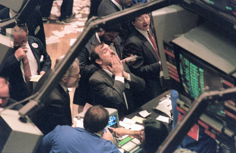 A trader (c) on the New York Stock Exchange looks at stock rates 19 October 1987 as stocks were devastated during one of the most frantic days in the exchange's history.  The Dow Jones index plummeted over 200 points in record trading. / AFP PHOTO / MARIA BASTONE