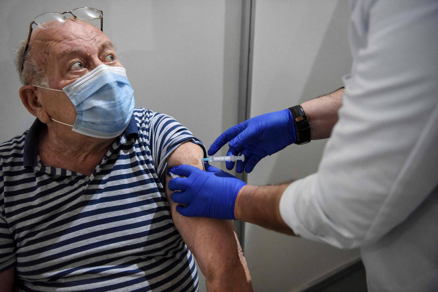 An elderly man receives a dose of the Sputnik V vaccine against the Covid-19 at the Boris Trajkovski sports hall in Skopje as the country start its vaccination campaign, after months of difficulties on April 16, 2021. Moscow announced on April 14, 2021 the start of production of its Sputnik V coronavirus vaccine in Serbia, the first European country outside Russia and Belarus to manufacture the vaccine. / AFP / Robert ATANASOVSKI