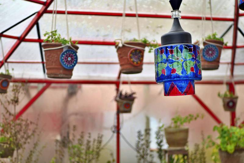 Pictured: Inside the new garden room at Taj Begum restaurant in Kabul hang plant pots and painted light shades. The restaurant has survived the Covid-19 pandemic but owner Laila Haidari is worried a deal between the Taliban and the Afghan government could put her business in jeopardy.  Photo by Charlie Faulkner