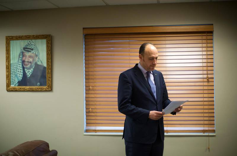 Husam Zomlot, the Palestinian envoy to Washington, reviews papers in Washington, Friday, Feb. 16, 2018. A few miles down the road from Israel's gated embassy, Zomlot sits in his office wrestling with a unique diplomatic dilemma: how to advance his people's cause at a time relations with the United States are so distant, he hasn't even spoken to the White House in months.(AP Photo/Pablo Martinez Monsivais)