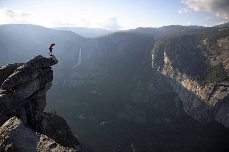 Alex Honnold peers over the edge of Glacier Point in Yosemite National Park. He had just climbed 2000 feet up from the valley floor. (National Geographic/Jimmy Chin)