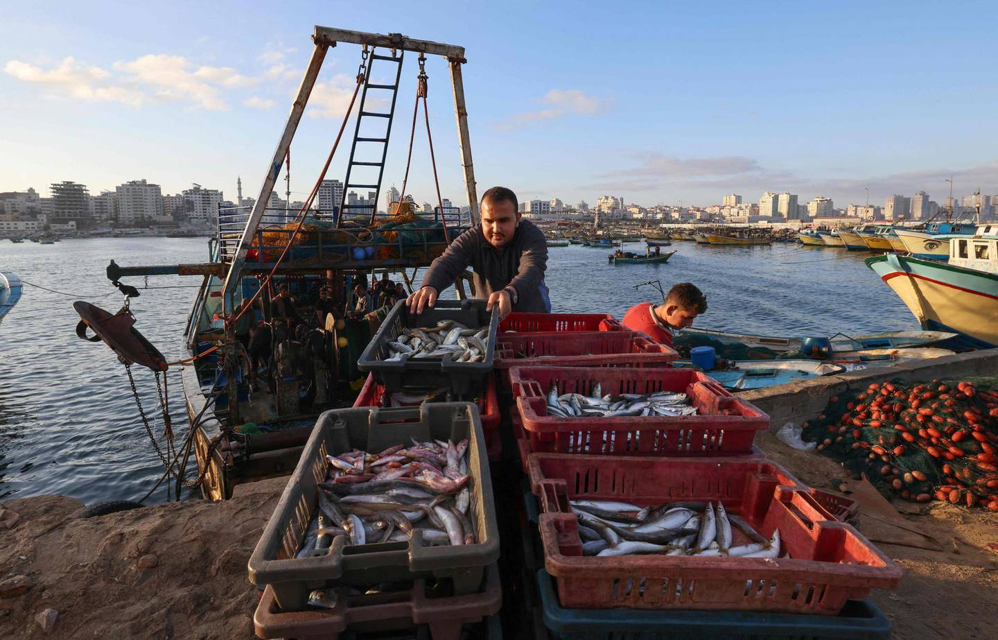 Palestinian fishermen unload their catch at Gaza City's main fishing port, on May 24, 2021, after Israeli security forces allowed a limited number of vessels to return to sea following a ceasefire in the recent conflict.  / AFP / Emmanuel DUNAND