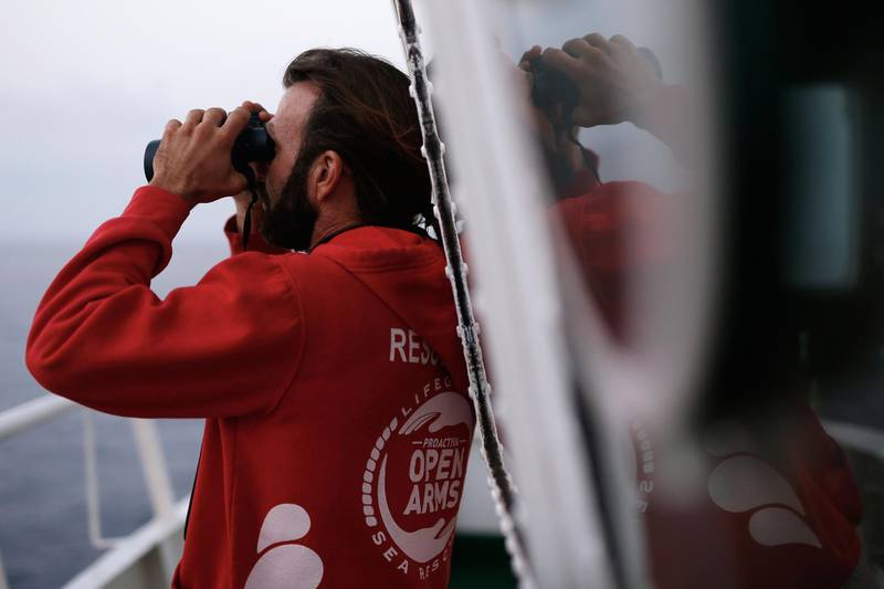 Spanish member of the Spanish NGO Proactiva Open Arms Jose Medina ises his binoculars as he searches for a rubber boat after a distress call on board of the Proactiva Open Arms rescue vessel in the Mediterranean open sea about 80 miles of the Libyan coast on July 17, 2018. / AFP / PAU BARRENA