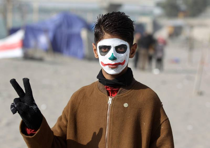 """TOPSHOT - An Iraqi protester wearing face-paint imitating DC comic and film character """"The Joker"""" poses for a picture near the sit-in by Senak bridge over the Tigris in the capital Baghdad on December 25, 2019.  / AFP / AHMAD AL-RUBAYE"""