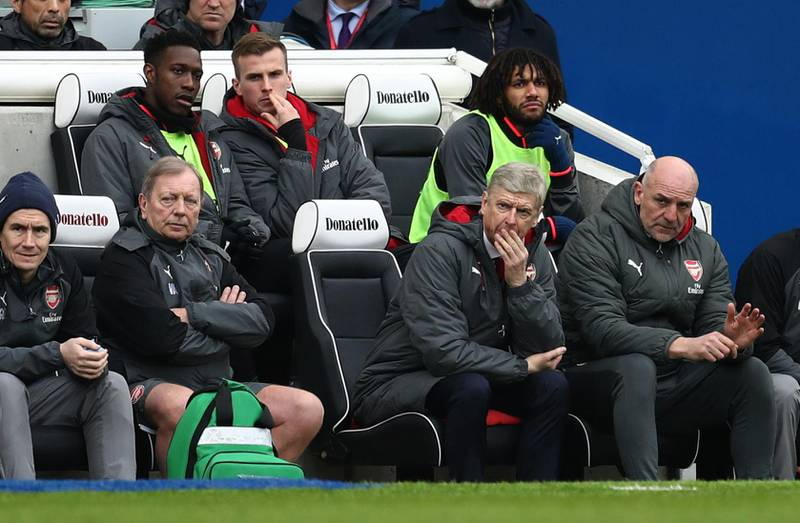 BRIGHTON, ENGLAND - MARCH 04: A tense looking Arsene Wenger manager / head coach of Arsenal watches the match with Danny Welbeck,Rob Holding and Mohamed Elneny of Arsenal on the bench behind him during the Premier League match between Brighton and Hove Albion and Arsenal at Amex Stadium on March 4, 2018 in Brighton, England. (Photo by Catherine Ivill/Getty Images)