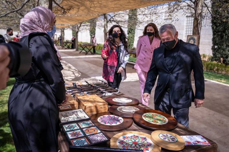 King Abdullah II, accompanied by Queen Rania Al Abdullah, views sample products from beneficiaries of the Productive Youth Initiative. Courtesy Royal Hashemite Court