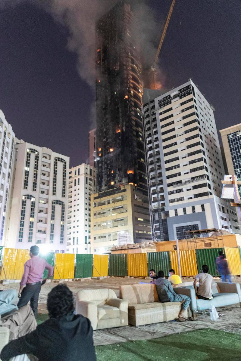 SHARJAH, UNITED ARAB EMIRATES. 05 MAY 2020. STANDALONE. Fire at the Abbco Tower near Nahda Park in Sharjah. Police and fire fighters responded to a blaze that was reported after 8:30. Men sit and watch the fire. (Photo: Antonie Robertson/The National) Journalist: Salam Al Amir. Section: National.
