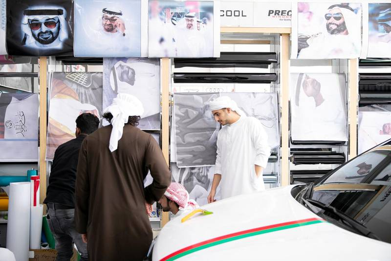ABU DHABI, UNITED ARAB EMIRATES - NOVEMBER 27, 2018.   Male university students shop for UAE National day accessories at Grand Plus Auto Accessories.  Car accessory shops in Mussafah are keeping busy as motorists rush to dress up their vehicles ahead of the UAE's 47th National Day.  (Photo by Reem Mohammed/The National)  Reporter:  HANEEN DAJANI Section:  NA