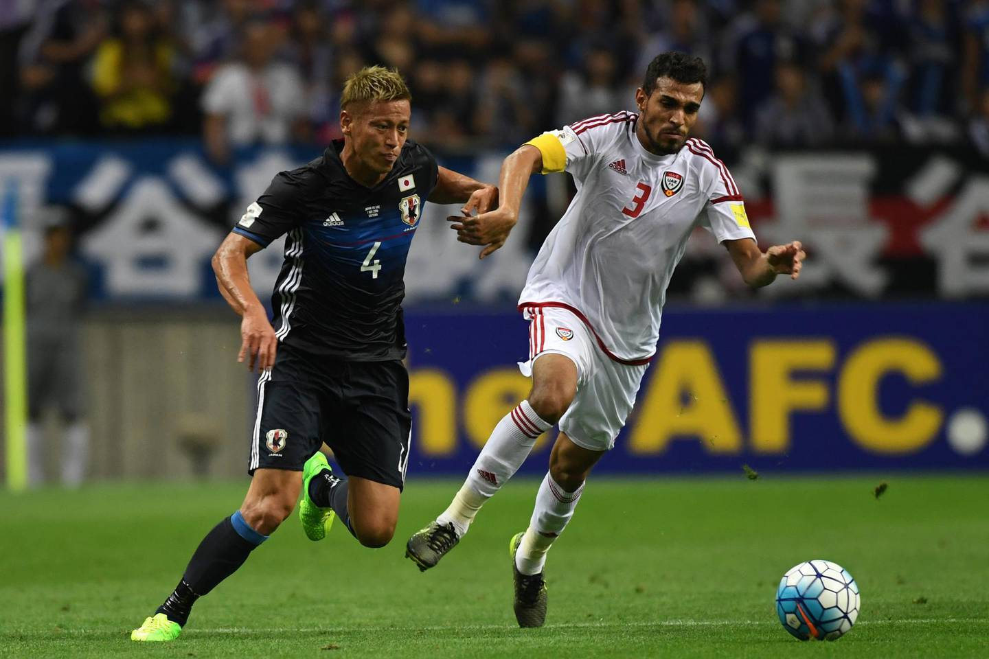 SAITAMA, JAPAN - SEPTEMBER 01: Walid Abbas of United Arab Emirates#3 and Keisuke Honda of Japan#4 compete for the ball during the 2018 FIFA World Cup Qualifiers Group B match between Japan and United Arab Emirates at Saitama Stadium on September 1, 2016 in Saitama, Japan. (Photo by Etsuo Hara/Getty Images)