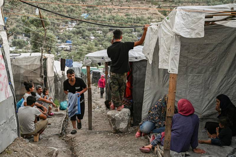 Refugees and migrants are pictured in a improvised tents camp near the refugee camp of Moria in the island of Lesbos on June 21, 2020. - Greece's announcement that it was extending the coronavirus lockdown at its migrant camps until July 5, cancelling plans to lift the measures on June 22, coincided with World Refugee Day on June 27, 2020. (Photo by ARIS MESSINIS / AFP)