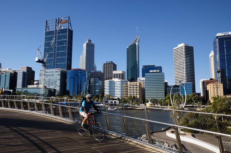 A cyclist rides along a deserted walkway in the normally busy Elizabeth Quay area in Perth on January 31, 2021, as authorities announced a snap five-day lockdown after a security guard at a quarantine hotel tested positive for Covid-19 ending Western Australia's ten month coronavirus-free streak. (Photo by TREVOR COLLENS / AFP)