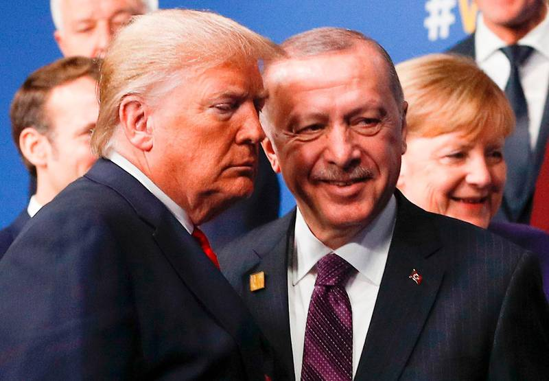 """(FILES) In this file photo taken on December 4, 2019, US President Donald Trump (L) and Turkey's President Recep Tayyip Erdogan (R) leave the stage after the family photo to head to the plenary session at the NATO summit at the Grove hotel in Watford, northeast of London. President Donald Trump has shattered through norms and niceties on the world stage in his nearly three years in office. Entering an election year, Trump is unlikely to slow down as he seeks what has largely eluded him -- a headline-grabbing victory. The tycoon turned president closes 2019 with a new stride after what was perhaps his most unambiguous achievement -- US commandos' raid that killed the leader of the Islamic State extremist group. But the year was also full of tosses and turns for Trump. On his ambition to end the war in Afghanistan, he startled Washington by inviting the Taliban to talks but then declared the talks dead before resuming them. / AFP / POOL / PETER NICHOLLS / TO GO WITH AFP STORY by Shaun TANDON, """"Trump on quest for foreign wins -- and drama -- in election year"""""""