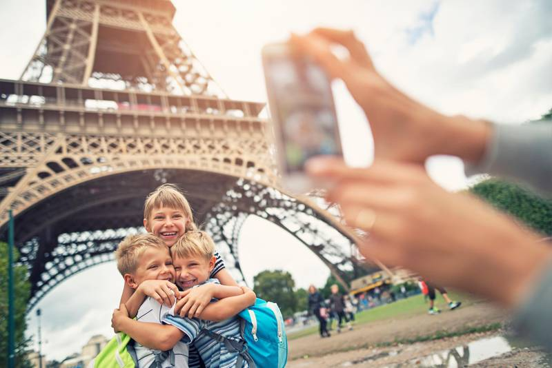 Mother taking picture of  little girl with her younger brothers hugging near The Eiffel Tower. The tower is visible in the background. The kids aged 9 and 6 are hugging and smiling at the camera. Paris, France. Getty Images