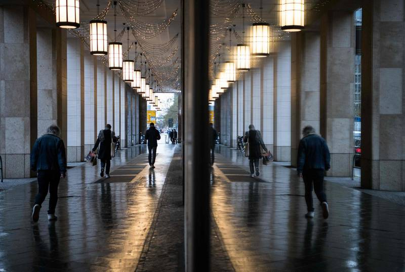 People reflect in windows as they walk through the arcades of a shopping mall where shops are closed during Germany's second lockdown amid the ongoing novel coronavirus / COVID-19 pandemic, on December 22, 2020 in Berlin, two days before Christmas. / AFP / STEFANIE LOOS