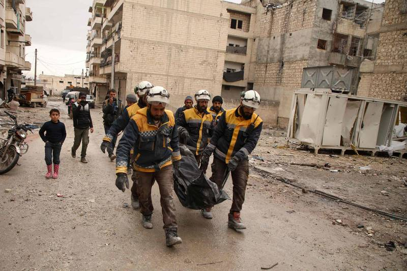 Members of the Syrian Civil Defence, also known as the White Helmets, carry the body of a woman recovered from the rubble of a building at the site of a reported airstrike on the rebel-held town of Ariha in the northern countryside of Syria's Idlib province early on January 30, 2020. Air strikes by government ally Russia hit near a bakery and a medical clinic in Syria's rebel-held Idlib region early on Thursday, killing 10 civilians, the Syrian Observatory for Human Rights said. At least five women were among the dead in the town of Ariha in Idlib province, where Russian-backed government forces are conducting an offensive against the country's last major rebel bastion. / AFP / AAREF WATAD