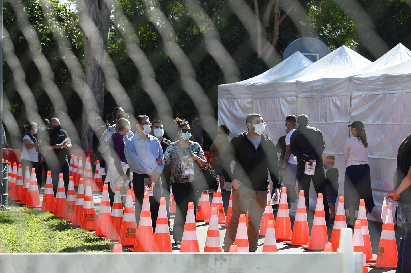 CORRECTION / People wait in long lines for coronavius tests at a walk-up Covid-19 testing site, November 24, 2020, in San Fernando, California, just northeast of the city of Los Angeles. California shattered the state's single-day COVID-19 record with over 20,500 new cases recorded on November 23 ahead of the Thanksgiving holiday. / AFP / Robyn Beck