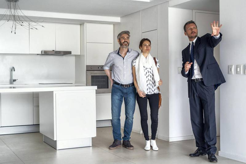 Real estate agent showing kitchen in new house to happy couple