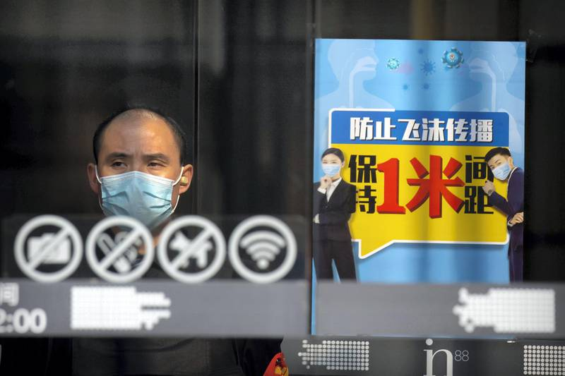 A security guard stands at the entrance of a shopping mall near a sign reminding people to keep at least one meter distance from each other in Beijing, Friday, Feb. 28, 2020. Japan's schools prepared to close for almost a month and entertainers, topped by K-pop superstars BTS, canceled events as a virus epidemic extended its spread through Asia into Europe and on Friday, into sub-Saharan Africa. (AP Photo/Mark Schiefelbein)