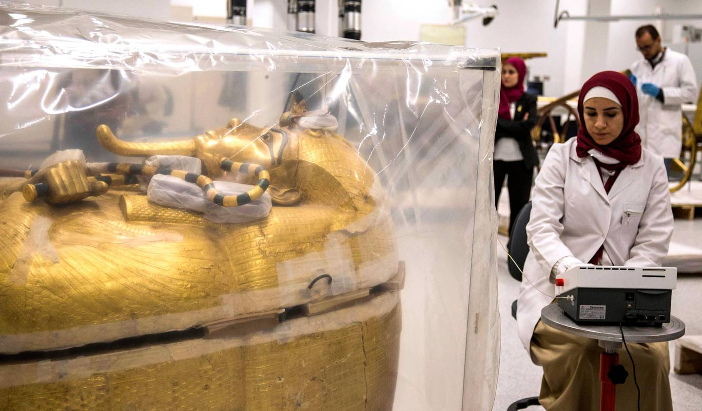 epa07755896 An Egyptian archeologist works next to the gilded coffin of King Tutankhamun that is undergoing a restoration process at the Grand Egyptian Museum in Giza, Egypt, 04 August 2019. The gilded coffin of king Tutankhamun was transported in mid-July from his tomb at the Valley of the Kings in Luxor to the Grand Egyptian Museum for an eight-month restoration process, the first since the tomb was discovered in 1922, before displaying among his treasured collection at the museum.  EPA/MOHAMED HOSSAM