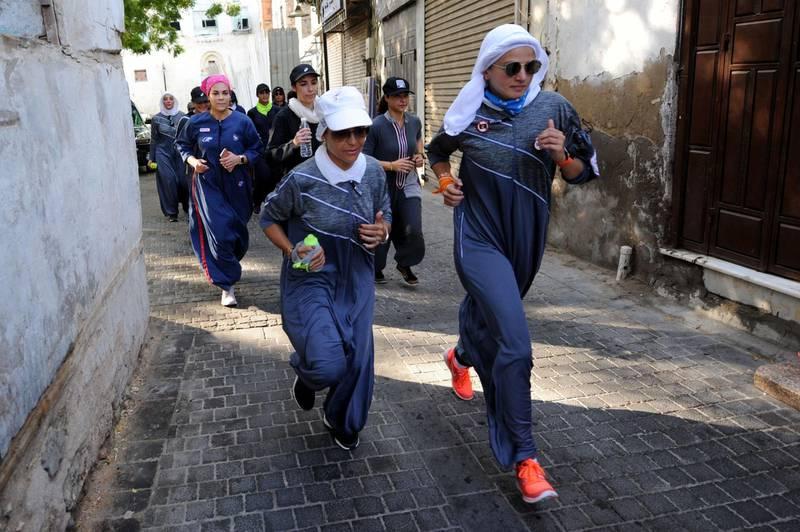Saudi women jog in the streets of Jeddah's historic al-Balad district on March 8, 2018. / AFP PHOTO / Amer HILABI