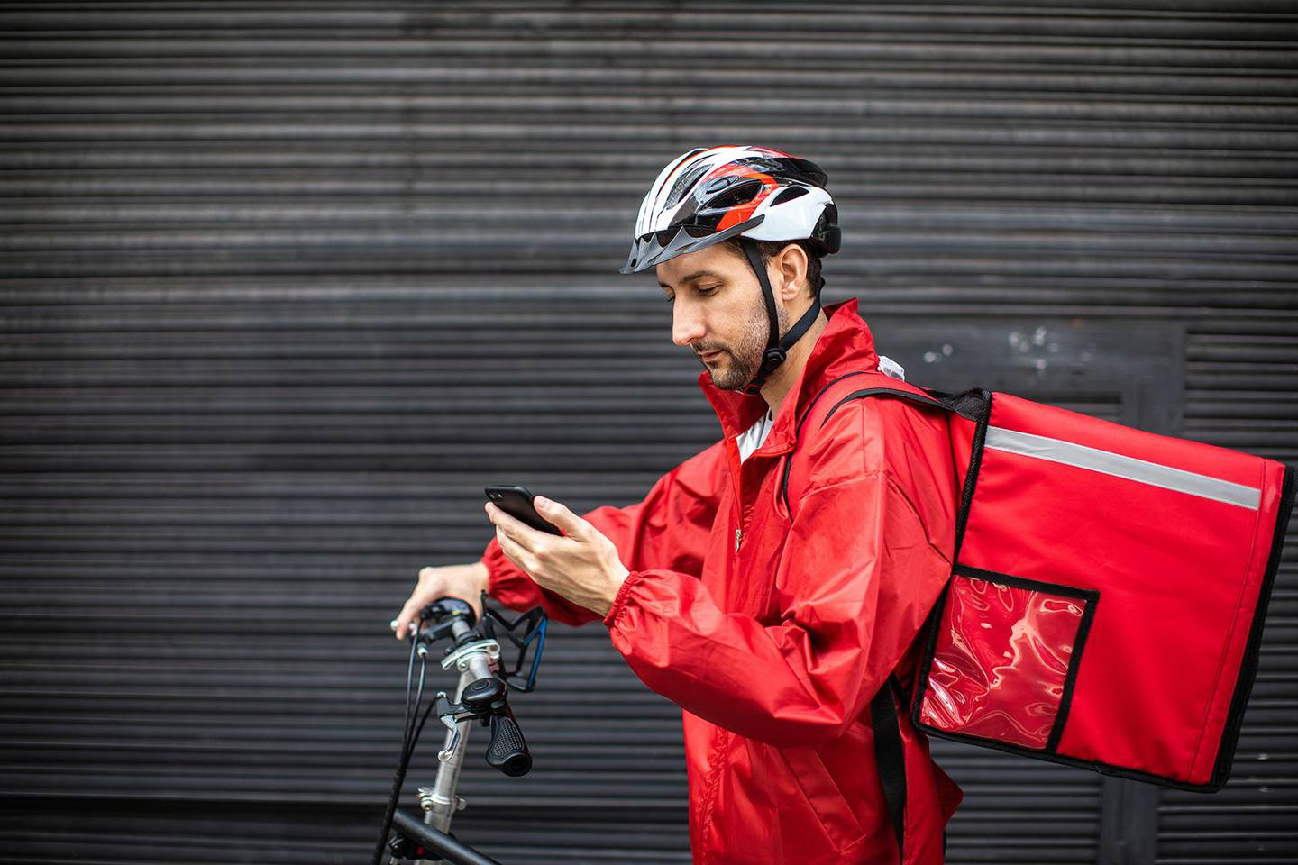 Male Bicycle delivery commuter with road bicycle in the city, using mobile phone to find customer location